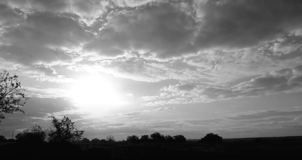 Black and white still of a rising sun through clouds over fields and a few trees..